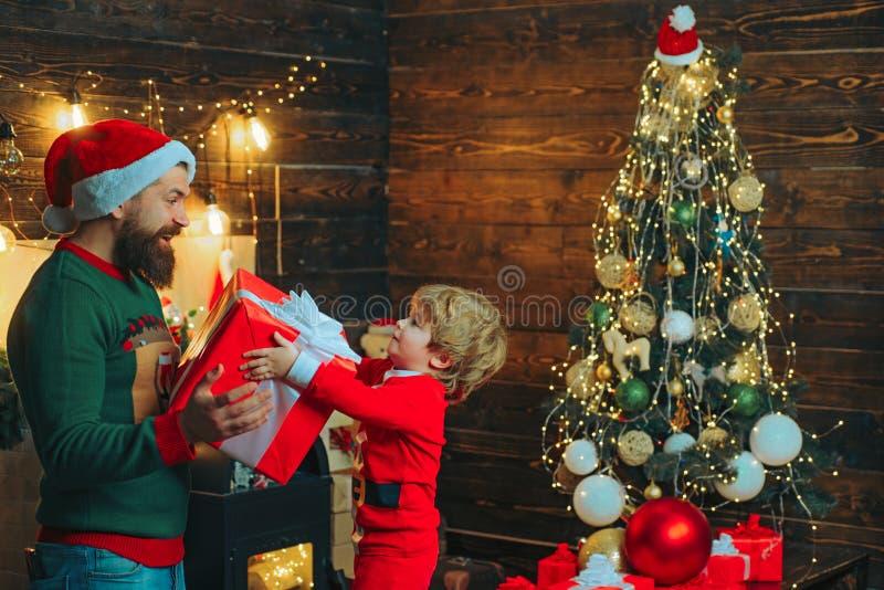De jonge geitjes genieten van de Kerstmisvakantie Gelukkige vader en zoon die Kerstboom verfraaien Kerstmis Family De voordien oc stock foto