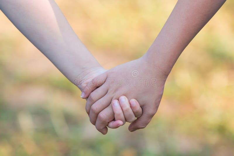 De jonge geitjes` handen die voor steun en vriendschap houden, vertroebelen groen gras stock afbeelding