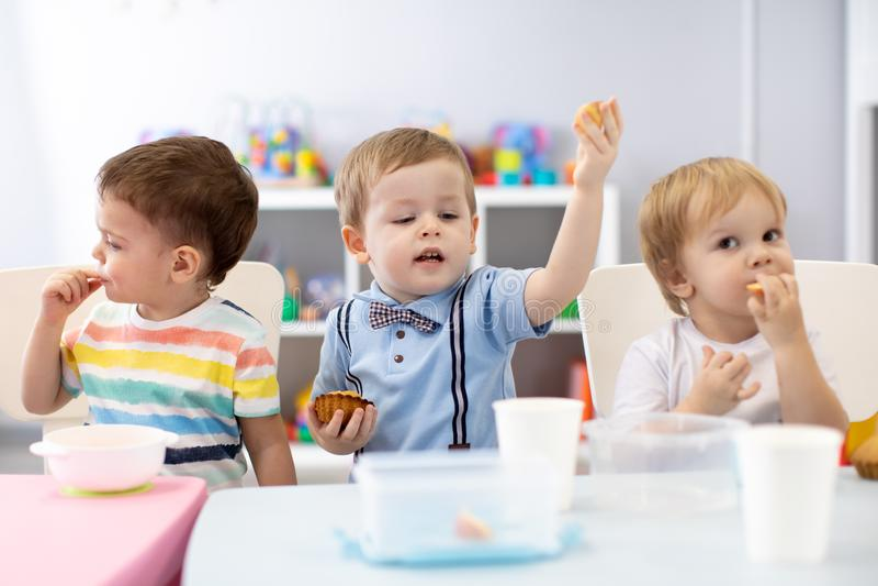De jonge geitjes hebben een lunch in opvangcentrum Kinderen die in kleuterschool eten stock fotografie