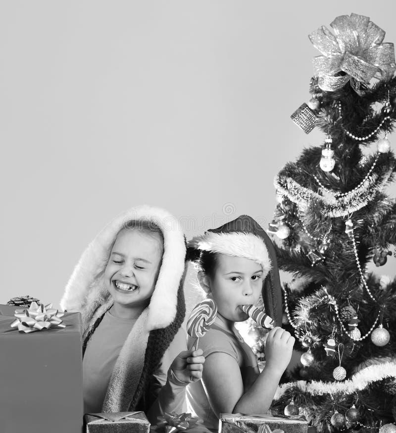 De jonge geitjes in Kerstmishoeden met open giftdozen stelt voor stock afbeelding