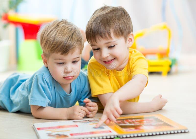 De jonge geitjes lezen thuis een boek of kinderdagverblijf stock foto