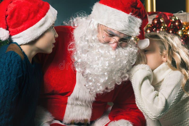 De jonge geitjes rond Santa Claus vertellen hem zij dit wenst, Kerstmisvooravond stock afbeeldingen