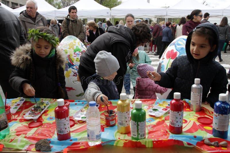 De jonge geitjes schilderen grote decoratieve eieren op workshop over Pasen-markt in de straat stock afbeeldingen