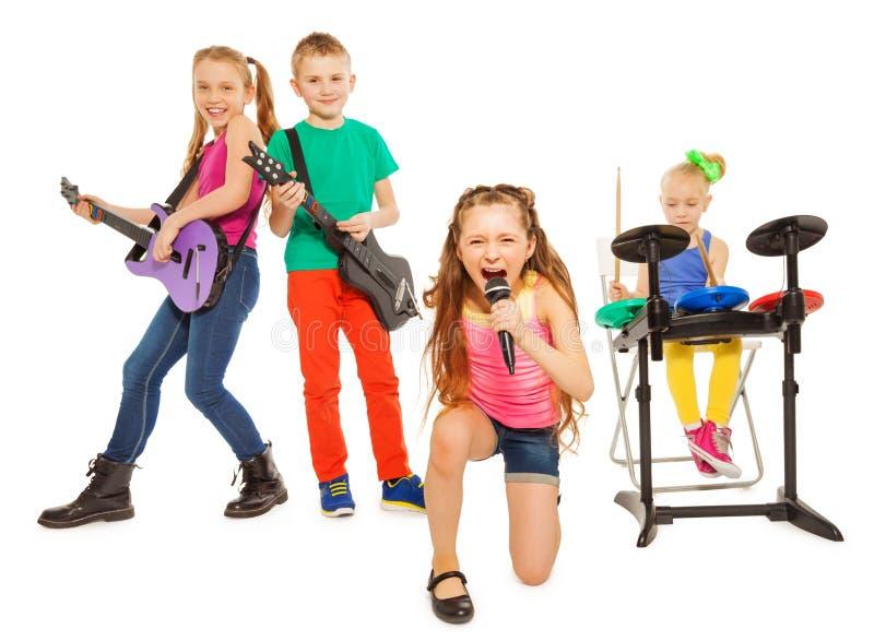 De jonge geitjes spelen muzikale instrumenten en het meisje zingt royalty-vrije stock foto