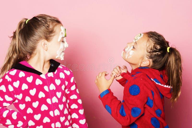 De jonge geitjes stellen op roze achtergrond Meisjes in polka gestippelde pyjama's royalty-vrije stock fotografie