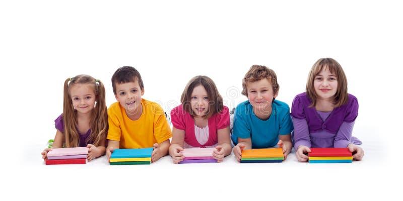 De jonge geitjes van de school met kleurrijke boeken royalty-vrije stock afbeeldingen