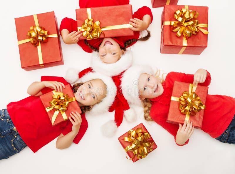 De jonge geitjes van Kerstmishelpers met rood stelt giftdoos voor  royalty-vrije stock afbeeldingen