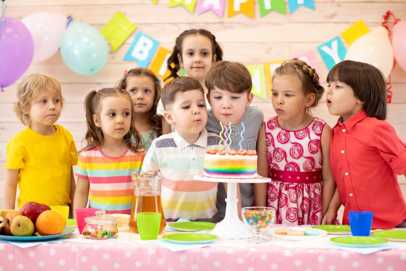 De jonge geitjes vieren verjaardagspartij en slagkaarsen op feestelijke cake stock foto