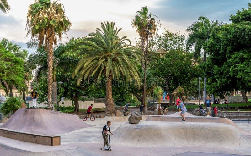De jonge geitjes voeren stunts op skateboards, autopedden en fietsen in het Park van La Granja, Santa Cruz de Tenerife uit, Canar royalty-vrije stock foto