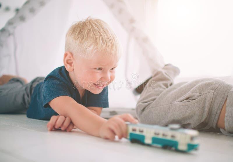 De jonge geitjesbroers leggen op de vloer De jongens spelen in huis met stuk speelgoed auto's thuis in de ochtend Toevallige leve royalty-vrije stock foto's