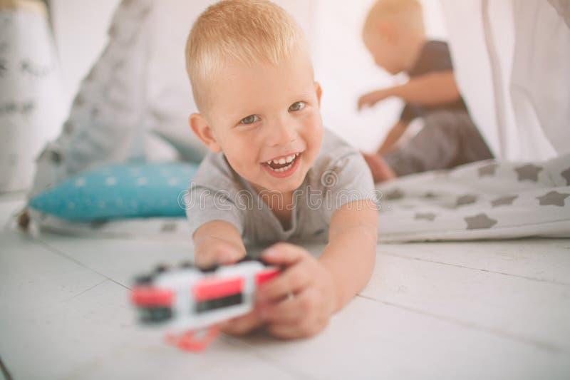 De jonge geitjesbroers leggen op de vloer De jongens spelen in huis met stuk speelgoed auto's thuis in de ochtend Toevallige leve stock foto's