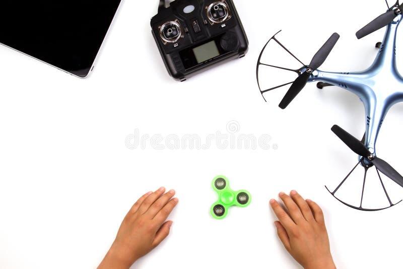 De jonge geitjeshanden, friemelen spinnerstuk speelgoed, hommel, verre controlemechanisme en tabletcomputer op witte achtergrond stock afbeelding