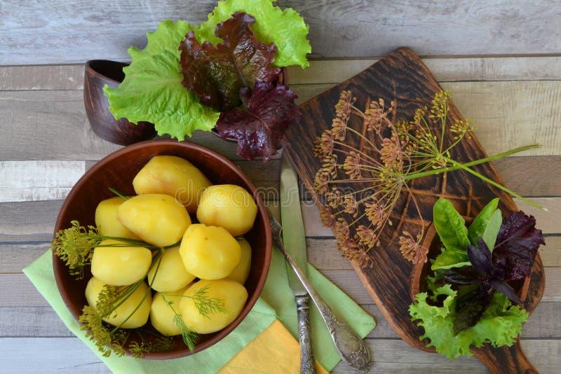 De jonge gekookte aardappels met boter en dille op een ceramische plaat in rustieke stijl, leggen vlak stock afbeelding