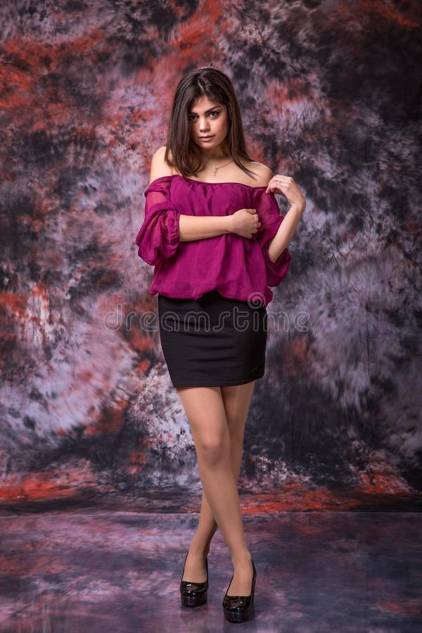 De jonge gekruiste wapens van de vrouwenholding Donkerbruin meisje in roze blouse De vrije tijdsmanier ontspant concept royalty-vrije stock foto