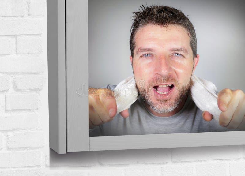 De jonge gelukkige aantrekkelijke handdoek van de mensenholding op zijn hals die vrolijk badkamersspiegel het glimlachen en posit stock afbeeldingen