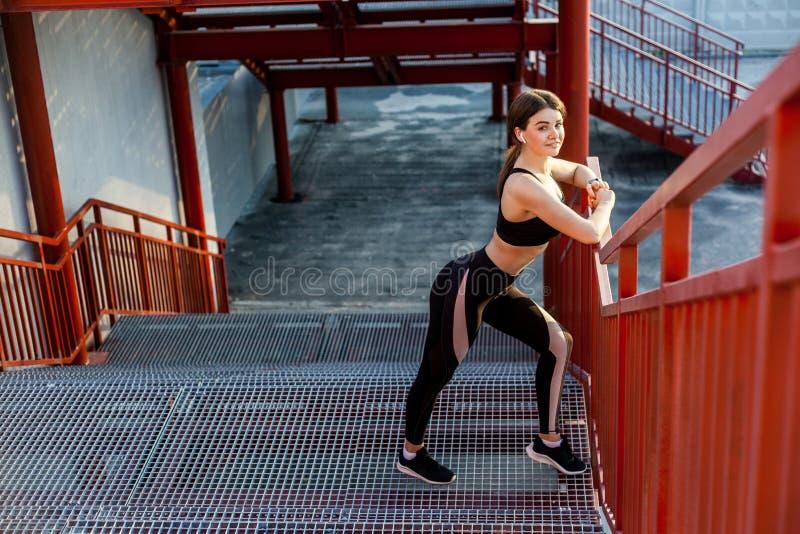 De jonge gelukkige atletische slanke mooie vrouw heeft een rust en status op treden na het doen van cardiointerval opleiding in z stock foto
