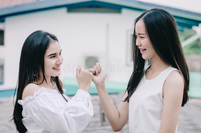 De jonge gelukkige Aziatische meisjes beste vrienden glimlachen zich het verenigen en vinger die, het teken van de conceptenvrien stock afbeeldingen