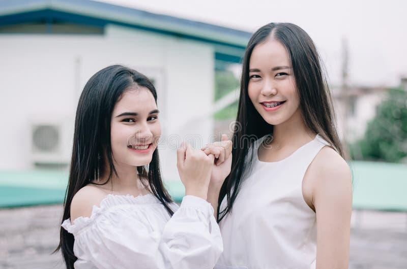 De jonge gelukkige Aziatische meisjes beste vrienden glimlachen zich het verenigen en vinger die, het teken van de conceptenvrien stock afbeelding
