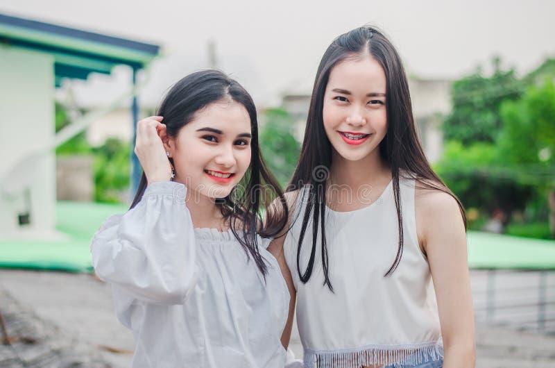 De jonge gelukkige Aziatische meisjes beste vrienden glimlachen zich het verenigen van en het hebben van pret bekijkend camera royalty-vrije stock afbeelding