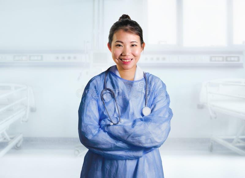 De jonge gelukkige en aantrekkelijke Aziatische Koreaanse geneeskunde artsenvrouw in blauw schrobt glimlachen vrolijk bij het bed stock fotografie