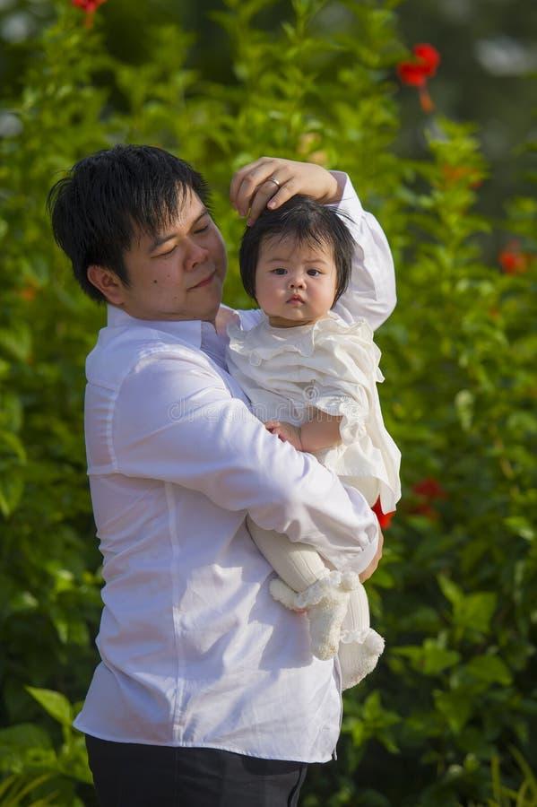 De jonge gelukkige en trotse mens als vader van snoepje weinig babymeisje die haar dochter voor bloemen houden tuiniert bij vakan stock afbeeldingen