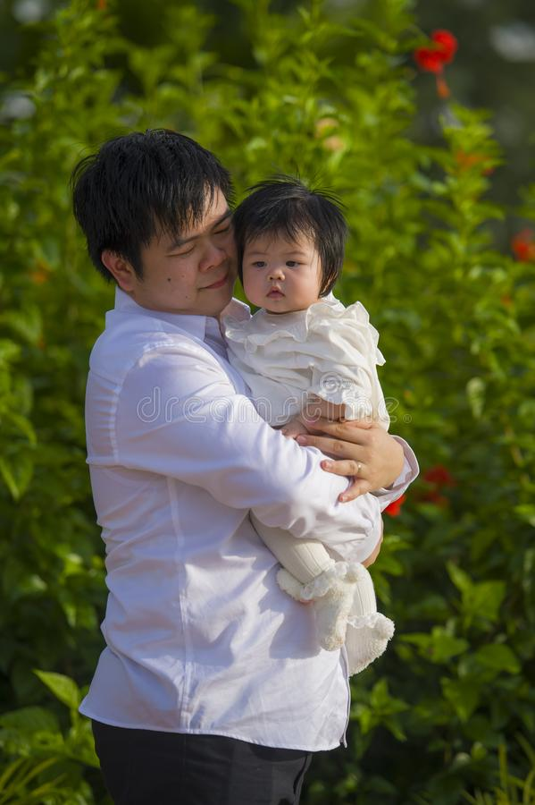 De jonge gelukkige en trotse mens als vader van snoepje weinig babymeisje die haar dochter voor bloemen houden tuiniert bij vakan royalty-vrije stock fotografie