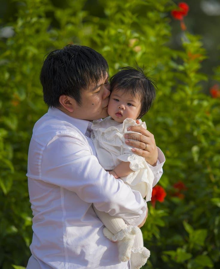 De jonge gelukkige en trotse mens als vader van snoepje weinig babymeisje die haar dochter voor bloemen houden tuiniert bij vakan stock foto's