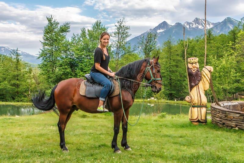 De jonge gelukkige glimlachende Kaukasische vrouw die jeans dragen berijdt bruin paard die en bij camera in de bergplatteland van royalty-vrije stock foto