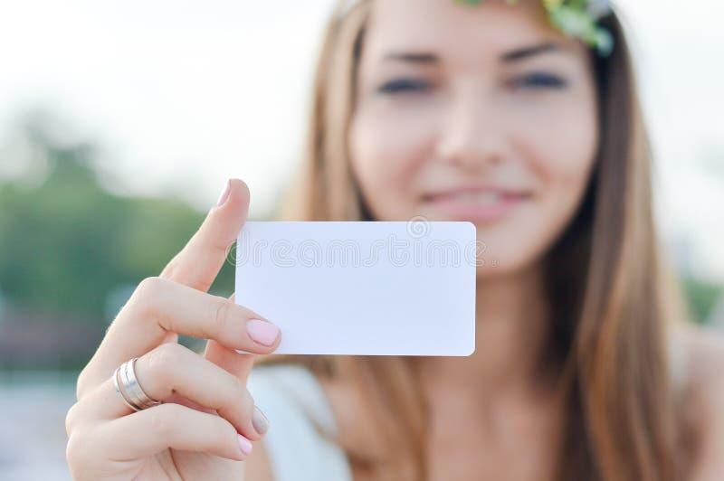 De jonge gelukkige glimlachende vrouw toont leeg adreskaartje royalty-vrije stock fotografie