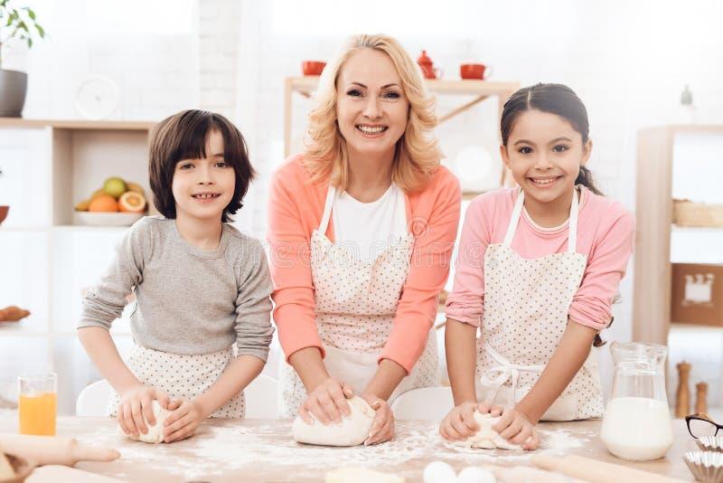 De jonge gelukkige grootmoeder samen met kleine gelukkige kleinkinderen kneedt deeg voor koekjes in keuken stock afbeeldingen