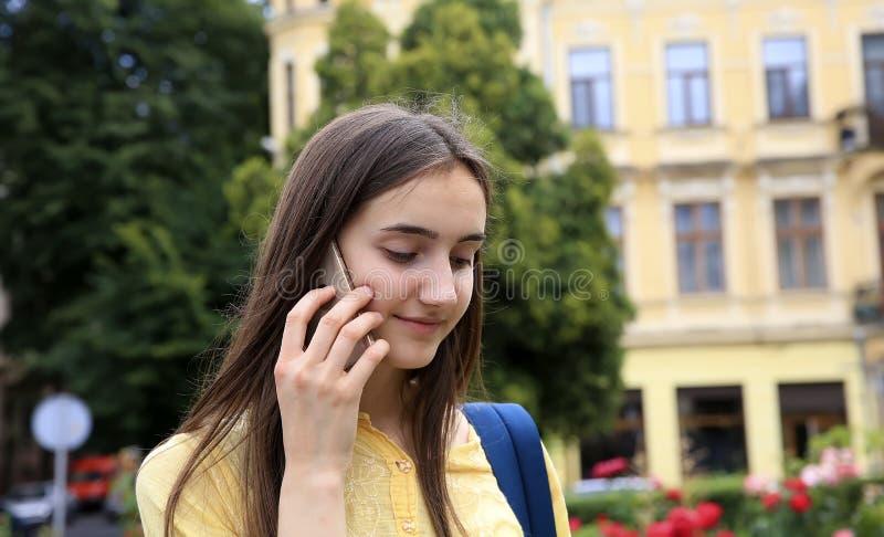 De jonge gelukkige Kaukasische vrouw roept met een mobiele telefoon in de stad stock foto