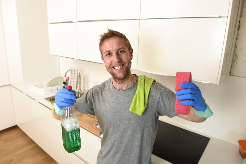 De jonge gelukkige mens in rubberwas gloves het houden van het detergent schoonmakende nevel en spons glimlachen royalty-vrije stock fotografie