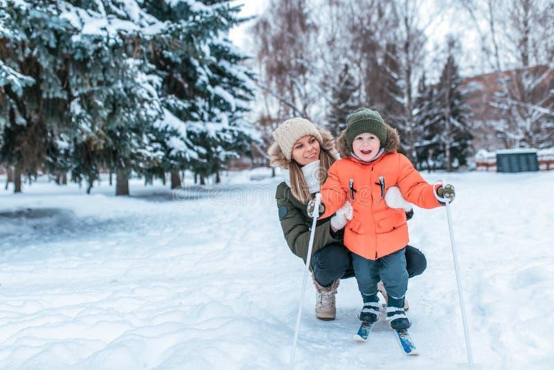 De jonge gelukkige moeder, een vrouw houdt een jongen 3-5 jaar de oude zoon, leert te skien In de winter in park buiten Vrije rui stock foto's