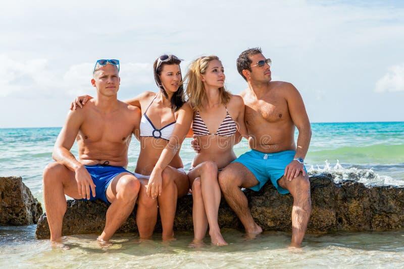De jonge gelukkige pret van vriendenhavin op het strand stock foto's