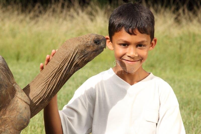 De jonge gelukkige schooljongen bezoekt een reuzeschildpad royalty-vrije stock fotografie