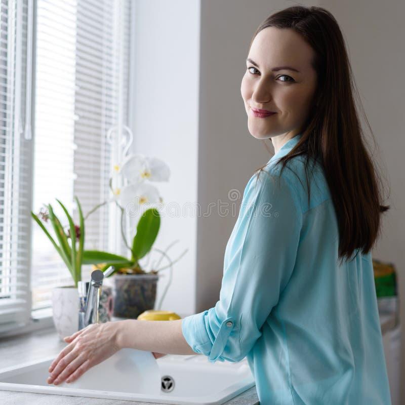 De jonge gelukkige schotels van de vrouwenwas in gootsteen voor venster, zacht vroeg ochtendlicht royalty-vrije stock foto's