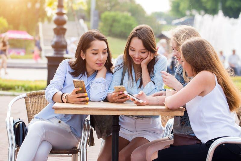 De jonge gelukkige studentenmeisjes gebruiken smartphones in het Park stock foto