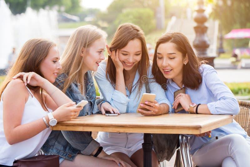 De jonge gelukkige studentenmeisjes gebruiken smartphones in het Park Een groep mooie glimlachende vrouwen die bij een lijst zitt stock foto's
