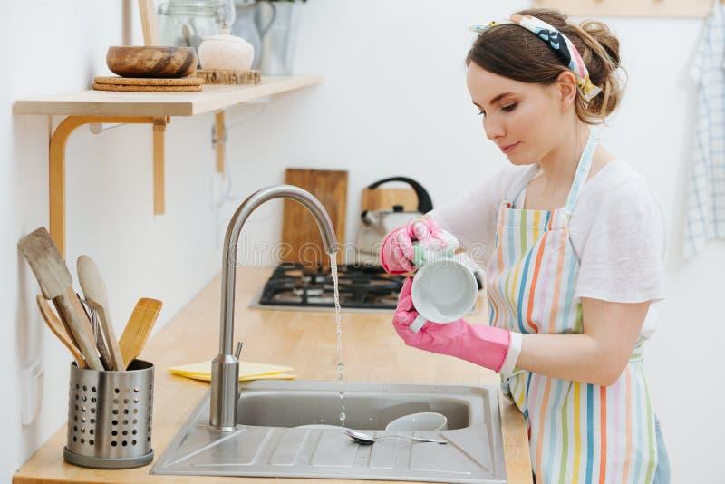 De jonge gelukkige vrouw in een keuken wast koppen en schotels royalty-vrije stock afbeelding