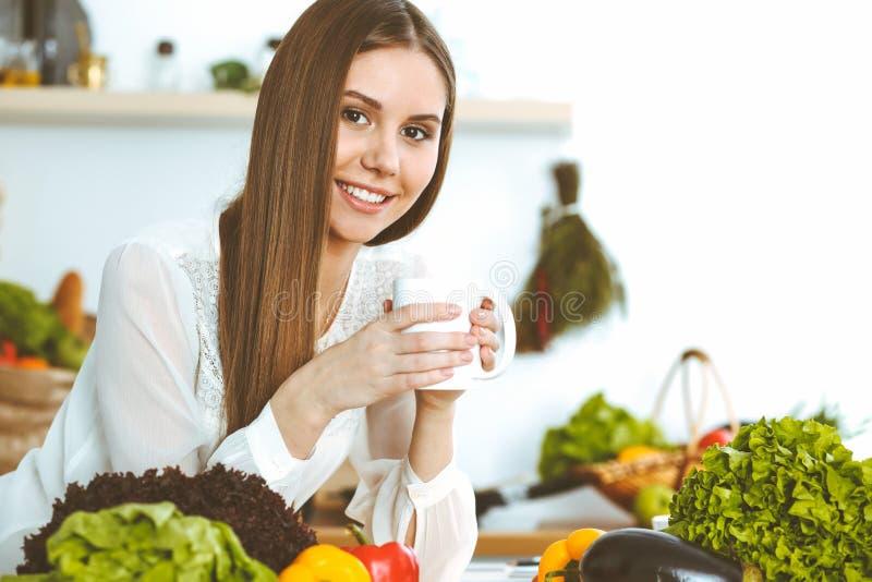 De jonge gelukkige vrouw houdt witte kop en bekijkt de camera terwijl het zitten bij houten lijst in de keuken onder stock foto