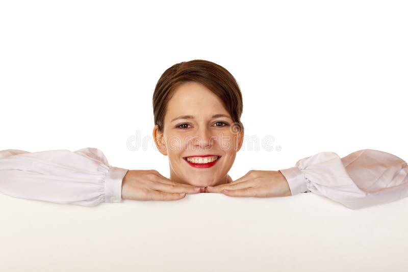 De jonge gelukkige vrouw leunt op leeg aanplakbord stock foto's
