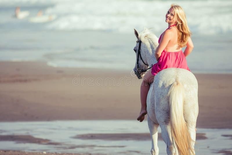 De jonge gelukkige vrouw ligt en koestert het paard stock fotografie