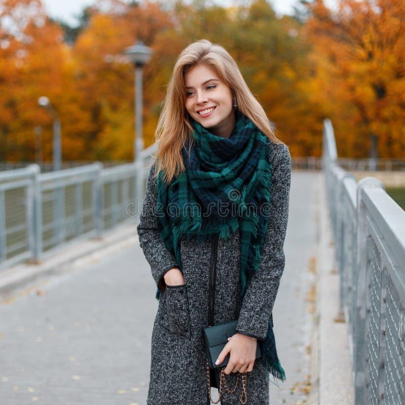 De jonge gelukkige vrouw met een mooie glimlach met blond haar in in elegante kleren met een handtas bevindt zich stock fotografie