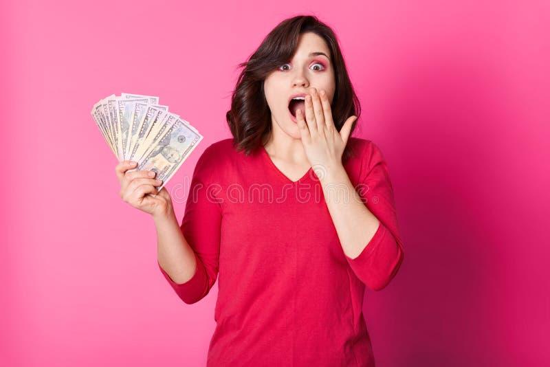 De jonge gelukkige vrouw met geld in hand, met geopende mond, kijkt verrast Donkerbruine meisjeswinsten in loterij Het gelukkige  stock fotografie