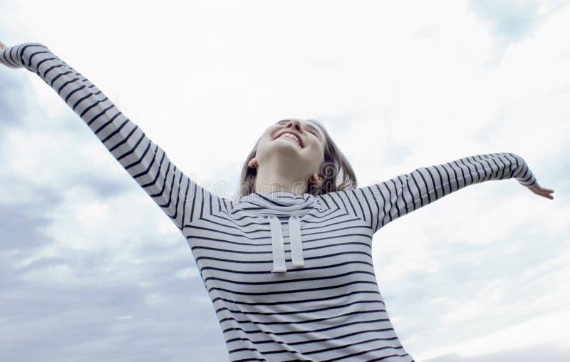 De jonge gelukkige vrouw opent haar wapens voor de blauwe hemel royalty-vrije stock fotografie