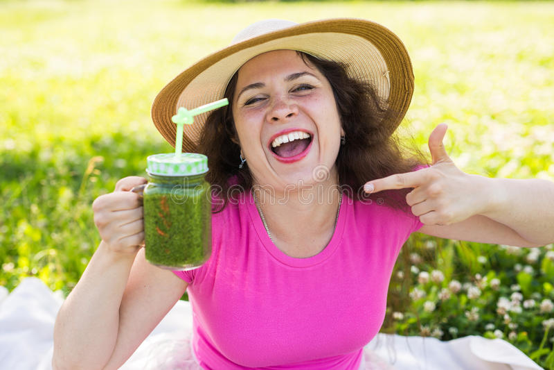 De jonge gelukkige vrouw toont op groene smoothies bij een picknick Gezond voedsel, detox en dieetconcept royalty-vrije stock afbeelding