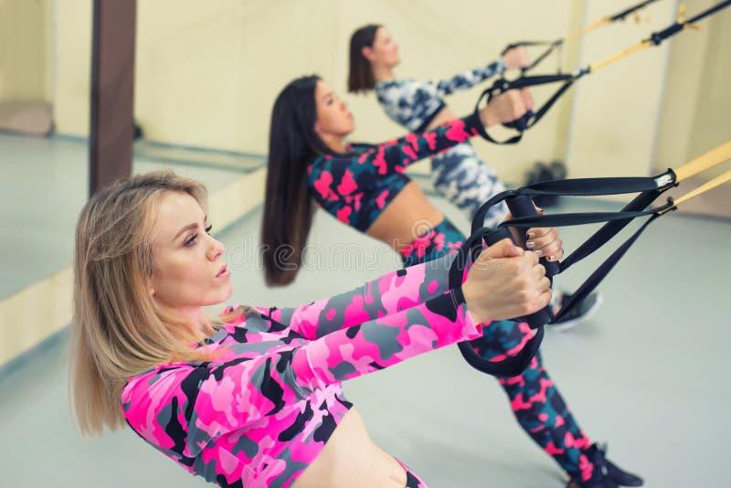 De jonge gelukkige vrouw voert opdrukoefeningen met opschortingsriemen, geschiktheidstraining bij gymnastiek uit royalty-vrije stock afbeelding