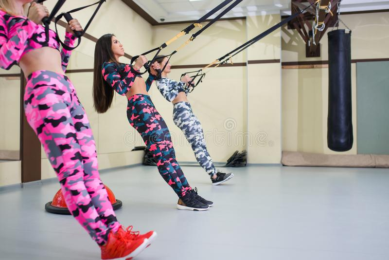 De jonge gelukkige vrouw voert opdrukoefeningen met opschortingsriemen, geschiktheidstraining bij gymnastiek uit royalty-vrije stock afbeeldingen
