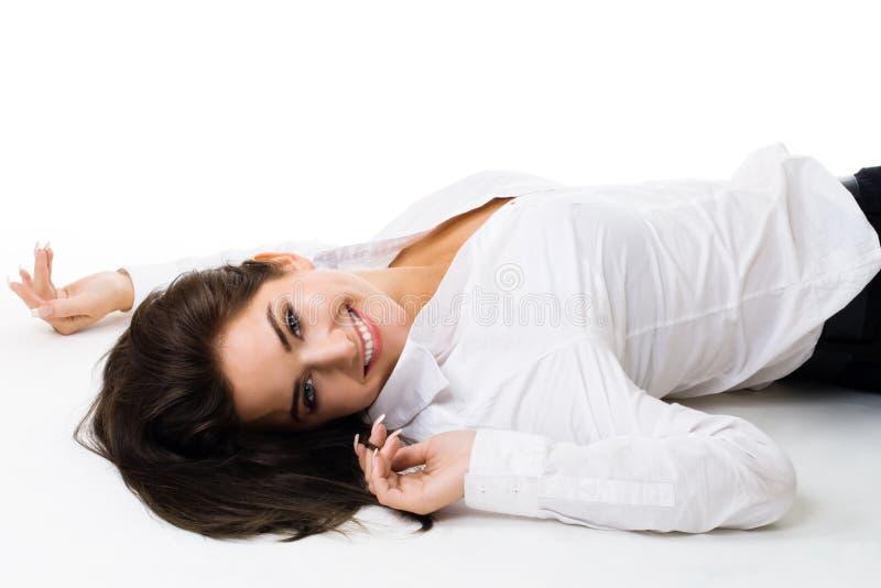 De jonge gelukkige vrouw in wit legt op de vloer stock afbeeldingen