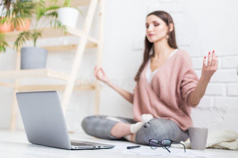 De jonge gelukkige vrouw zit op de vloer in een yoga stelt in een helder flat en het werk achter laptop, een freelancermeisje stock foto
